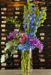 over 2' tall and is filled with premium flowers such as Shocking Blue Hydrangea, Pink Ming Tropical Protea, Bells of Ireland, Electrifying Puirple Phalaenopsis Orchids, and Brilliant Blue Delphinium